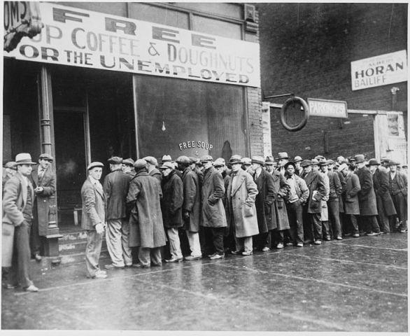 """Una multitud de hombres desempleados esperan su turno para obtener alimentos de beneficencia. Chicago, febrero de 1931. Notas curiosas: obsérvese que en la cola esperan tanto blancos como afroamericanos. Juntos. esa sala de beneficencia fue costeada por el famosísimo gangster Al Capone. En el cartel puede leerse: """"sopa, café y donuts gratis para los desempleados""""."""