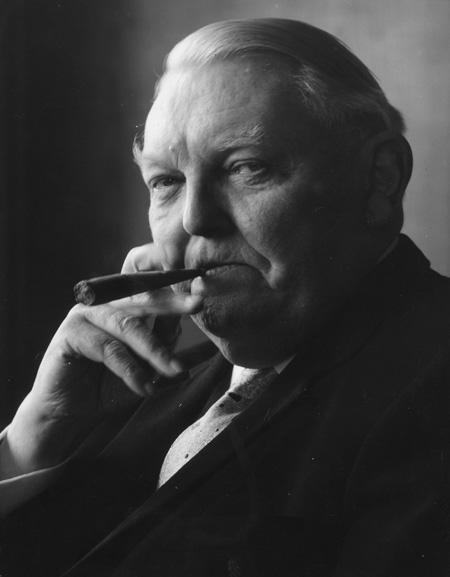 Ludwig Erhard (1897-1977), fumando uno de sus icónicos puros. Economista y político alemán cercano a la Unión Demócrata-Cristiana (en la que acabaría por integrarse), fue nombrado ministro de Economía del gobierno bávaro (1945), director económico de las zonas de ocupación británica y norteamericana (1948), diputado en el Parlamento de la recién creada República Federal Alemana (1949) y ministro de Economía del gobierno Adenauer (1949). Fue canciller alemán en sustitución de éste entre 1963 y 1966, retirándose después de la política.