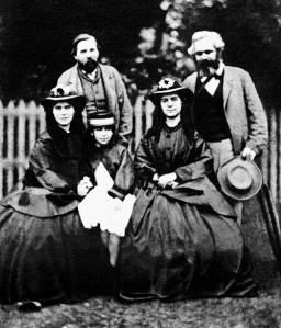 Karl Marx (atrás, derecha) junto con Friedrich Engels (atrás, izquierda), con las hijas de Marx: Jenny Caroline, Jenny Julia Eleanor, y Jenny Laura. Junio de 1864.