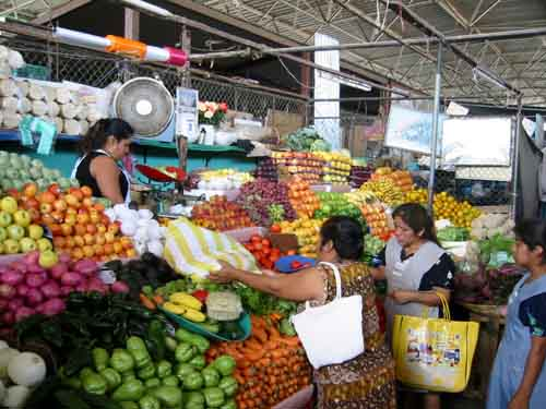 Escena cotidiana en el mercado de Puerto Escondido, Oaxaca México. Cuando se efectúa una tarnsacción, se revelan dos funciones al observador: lo que valora el comprador el prodducto y lo que le cuesta desprenderse de ese producto al vendedor.